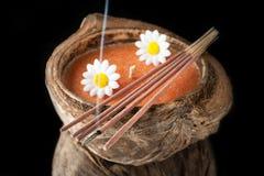 Aromakerze in der Kokosnuss und in den Räucherstäbchen. Stockfoto