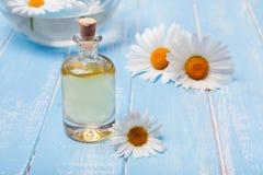 Aromaöl- und -kamillenblumen auf blauem hölzernem Hintergrund Lizenzfreie Stockfotografie