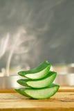 Aromaterapia con le fette fresche di vera dell'aloe su di legno. Immagine Stock