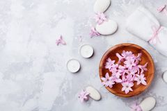 A aromaterapia, termas, fundo da beleza com seixo da massagem, perfumou flores molha e velas na opinião de tampo da mesa de pedra fotos de stock