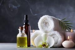 Aromatherapie, Badekurort, Schönheitsbehandlung und Wellnesshintergrund mit Massageöl, Orchideenblumen, Tücher, kosmetische Produ stockfotografie