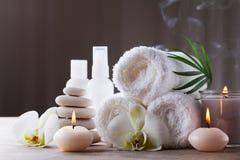Aromatherapie, Badekurort, Schönheitsbehandlung und Wellnesshintergrund mit Massagekieseln, Orchideenblumen, Tücher, kosmetische  lizenzfreies stockfoto