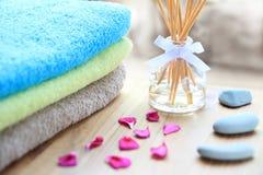 Aromatherapie Reeddifuserflasche auf einem Holztisch mit Tüchern, den Blumenblättern und den Massagesteinen Stockbild