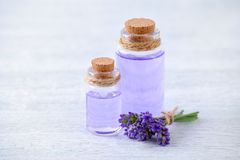 Aromatherapy πετρέλαιο μπουκαλιών γυαλιού και φρέσκα lavender λουλούδια στον ξύλινο πίνακα Στοκ Εικόνα