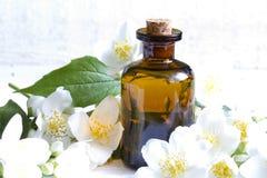 Aromatherapy πετρέλαιο της Jasmine στις άσπρες σανίδες με τα λουλούδια Στοκ Φωτογραφία