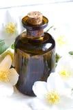 Aromatherapy πετρέλαιο της Jasmine στις άσπρες σανίδες με τα λουλούδια Στοκ Εικόνες