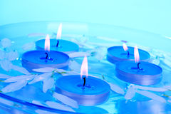 Aromatherapy. Candles and petals floating in a glass bowl royalty free stock photos