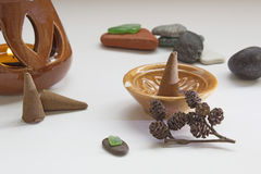 Aromatherapy accessories still life. Aromatherapy accessories: aroma lamp, cone in a ceramic stand and a few spa stones on a white matte background Stock Photos
