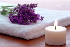 Aromatherapy Candle and Lavender Flowers in a spa. Aromatherapy candle burning with a soft glow flame and fresh lavender flowers on a soft white towel in a stock photo