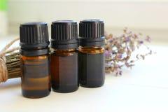 Aromatherapy De kruiken van etherische oliën en een boeket van lavendel bloeit op een witte achtergrond stock afbeeldingen