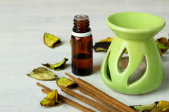 Aromatherapy. Decorative vase with a candle and a jar with essential oils with the incense on white wooden background Royalty Free Stock Photography