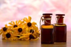 Aromatherapy Flasche mit Blumen-Hintergrund Stockfotos