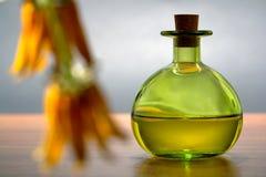 Aromatherapy Flasche mit Blumen-Vordergrund stockfotografie