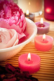Aromatherapy flowers and candles. A bowl full of beautiful pink aromatherapy flowers with candles. Spa scene Royalty Free Stock Image