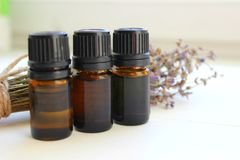 Aromatherapy. Jars of essential oils and a bouquet of lavender flowers on a white background. stock images