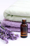 Aromatherapy oil and lavender. Flowers against terry towels Royalty Free Stock Image
