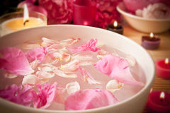 Aromatherapy oils, flower petals, candles. An arometherapy scene, with aromatic oils and petals in the water and candles. Focus on the petals. Spa scene Stock Photo