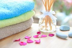 Aromatherapy reed difuser bottle on a wooden table with towels, petals and massage stones Stock Images