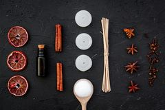 Aromatherapy for relax concept. Spa salt, candles and oil with spices cinnamon on black background top view Stock Images