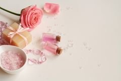 Aromatherapy. Small glass bottles with cosmetic oils. Bath salt. Fresh rose. Objects spa procedures on white background oil, flower, salt.r Stock Image
