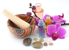 Aromatherapy spa. Orchid, wooden mortar and pestle, healing stones and botanical bottles, ready for you beauty needs Royalty Free Stock Photos