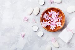 Aromatherapy, spa, beauty background with massage pebble, perfumed flowers water and candles on stone table from above. Relaxation and zen like concept. Flat Stock Image