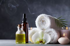 Aromatherapy, spa, beauty treatment and wellness background with massage oil, orchid flowers, towels, cosmetic products