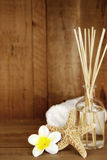 Aromatherapy Still Life. Aromatherapy bottle and reeds, with towl, frangipani and seashell, over timber.  Soft focus Royalty Free Stock Photo