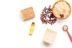 Aromatherapy und Badekurortkonzept Badekurortsalz mit Kaffeegeruch nahe Seife, Badekurortöl und Luffa auf weißer Draufsichtkopie  stockfoto