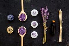 Aromatherapy voor ontspant concept Lavendeltak, kuuroordzout, olie en kaarsen op zwarte hoogste mening als achtergrond royalty-vrije stock afbeeldingen