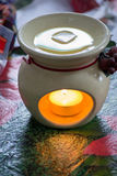 Aromatherapy Wax Melter. Tranquil tea light candle burning in aromatherapy burner with scented wax melting Stock Photos