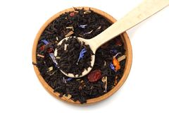 Aromatic black dry tea with petals in wooden spoon isolated on white background Royalty Free Stock Photos