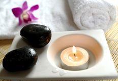 Aromatic candle. Stones, orchid and a white towel Stock Images