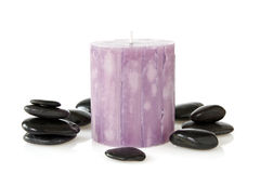 Aromatic candle and black pebbles Stock Photos