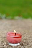 Aromatic candle burning. On garden pavement Stock Images