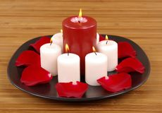 Aromatic Candles. And rose petals on bamboo Royalty Free Stock Photo