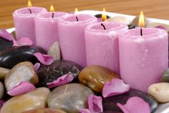 Aromatic Candles. Pink aromatic candles and rose petals on pebbles Royalty Free Stock Photo