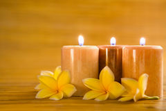 Aromatic candles with frangipani on bamboo mat Royalty Free Stock Photography