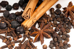 Aromatic Christmas spices. Three cinnamon sticks surrounded by a variety of dried Christmas spices: peppercorns, star anise, cloves and juniper berries Stock Photo