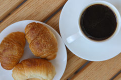 Aromatic coffee and croissants on a plate. Wooden background Stock Photography