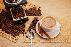 Aromatic coffee, natural grain, Arabica, cinnamon stick. Aromatic coffee, natural grain, Arabica. Shows a hot Cup of coffee, coffee beans, hand grinder and men`s stock photo