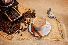 Aromatic coffee, natural grain, Arabica. Shows a hot Cup of coffee, coffee beans, hand grinder and men& x27;s mechanical pocket watch with hinged lid royalty free stock images
