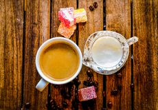 Aromatic coffee in a white cup with a glass milk jug next to it, stock photo