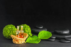 Aromatic concept of bergamot, leaf, fragrance oil and zen basalt Royalty Free Stock Photos