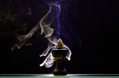 Aromatic cone smoldering in a ceramic stand Royalty Free Stock Photos