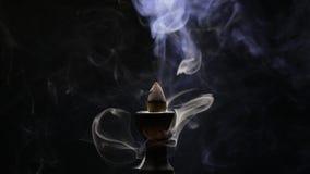 Aromatic cone smoldering in a ceramic stand stock video