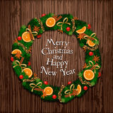 Aromatic Decorated Christmas Wreath on Wooden Door. Evergreen wreath on door. Christmas wreath of Xmas tree branches with garlands, orange and spices on wooden Stock Photo