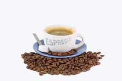 Aromatic Expresso. Expresso coffee with sugar over roasted coffee beans Royalty Free Stock Photo