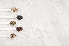 Aromatic food cooking ingredients. Black and white pepper, clove, savory, fennel seeds. Top view, free space. Different spices and herbs in wooden spoons on Royalty Free Stock Photo