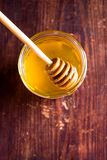 Aromatic honey with wooden honey dipper in a jar on a wooden table, selective focus, closeup. Healthy and organic food option. Ima. Ge with copy space stock photo